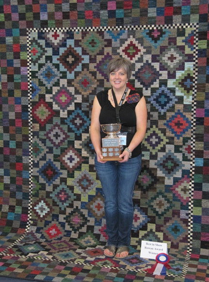 Jen Manuell accepts award for multi color pattern hooked-rug